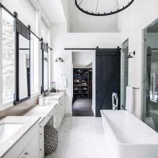 Ispirazione per una stanza da bagno padronale minimalista di medie dimensioni con ante lisce, ante bianche, vasca freestanding, doccia alcova, WC monopezzo, pareti bianche, pavimento in marmo, lavabo da incasso, top in granito, pavimento bianco, porta doccia a battente e top beige
