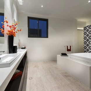 Large minimalist master white tile and mosaic tile travertine floor drop-in bathtub photo in Miami with a trough sink, flat-panel cabinets, dark wood cabinets, recycled glass countertops and white walls