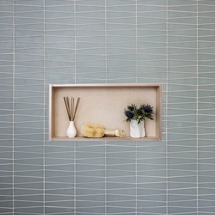 Inspiration for a small modern beige tile and porcelain tile bathroom remodel in San Francisco with flat-panel cabinets, light wood cabinets, a one-piece toilet, beige walls, an integrated sink and solid surface countertops