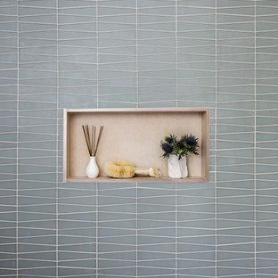Идея дизайна: маленькая ванная комната в стиле модернизм с плоскими фасадами, светлыми деревянными фасадами, накладной ванной, душем над ванной, унитазом-моноблоком, бежевой плиткой, керамогранитной плиткой, бежевыми стенами, монолитной раковиной, столешницей из искусственного камня и шторкой для ванной