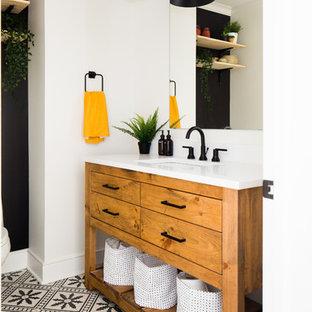 Modelo de cuarto de baño con ducha, ecléctico, pequeño, con armarios con paneles lisos, puertas de armario de madera oscura, paredes blancas, suelo de azulejos de cemento, encimera de mármol, suelo negro y encimeras blancas