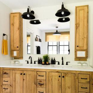 ローリーの広いトランジショナルスタイルのおしゃれなマスターバスルーム (シェーカースタイル扉のキャビネット、中間色木目調キャビネット、猫足バスタブ、オープン型シャワー、分離型トイレ、白いタイル、白い壁、セメントタイルの床、アンダーカウンター洗面器、ライムストーンの洗面台、白い床、開き戸のシャワー、白い洗面カウンター) の写真