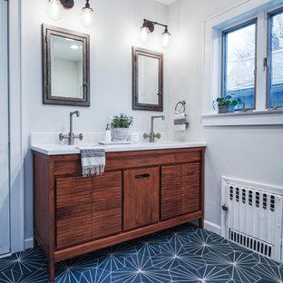 ニューヨークの広いエクレクティックスタイルのおしゃれなマスターバスルーム (中間色木目調キャビネット、アルコーブ型浴槽、アルコーブ型シャワー、グレーの壁、セメントタイルの床、クオーツストーンの洗面台、ターコイズの床、白い洗面カウンター、洗面台2つ、独立型洗面台) の写真