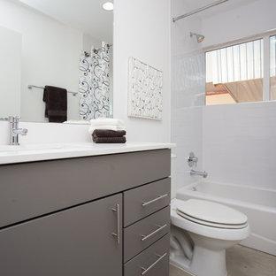 Foto de cuarto de baño con ducha, minimalista, de tamaño medio, con armarios con paneles lisos, puertas de armario blancas, bañera empotrada, ducha empotrada, sanitario de una pieza, baldosas y/o azulejos blancos, baldosas y/o azulejos de cemento, paredes blancas, suelo de cemento, lavabo bajoencimera y encimera de esteatita