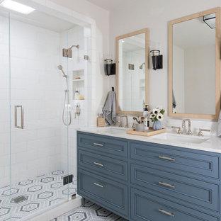 Bild på ett stort vintage vit vitt en-suite badrum, med möbel-liknande, blå skåp, en dusch i en alkov, vit kakel, tunnelbanekakel, mosaikgolv, ett undermonterad handfat, bänkskiva i kvarts, flerfärgat golv och dusch med gångjärnsdörr