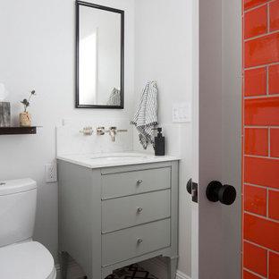 Klassisk inredning av ett mellanstort vit vitt badrum, med släta luckor, grå skåp, en dusch i en alkov, en toalettstol med separat cisternkåpa, orange kakel, keramikplattor, grå väggar, klinkergolv i keramik, ett undermonterad handfat, marmorbänkskiva, flerfärgat golv och med dusch som är öppen