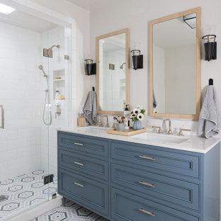 Idéer för att renovera ett stort vintage vit vitt en-suite badrum, med möbel-liknande, blå skåp, en dusch i en alkov, vit kakel, tunnelbanekakel, mosaikgolv, ett undermonterad handfat, bänkskiva i kvarts, flerfärgat golv och dusch med gångjärnsdörr