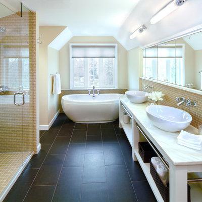 Elegant yellow tile black floor freestanding bathtub photo in Minneapolis with a vessel sink and beige walls