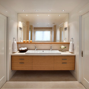 Example of a trendy limestone floor bathroom design in San Francisco with a trough sink and marble countertops
