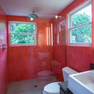Foto di una grande stanza da bagno padronale minimalista con ante lisce, ante marroni, vasca ad angolo, doccia alcova, pareti rosse, pavimento in cemento, lavabo a bacinella, top in granito, pavimento grigio e doccia aperta