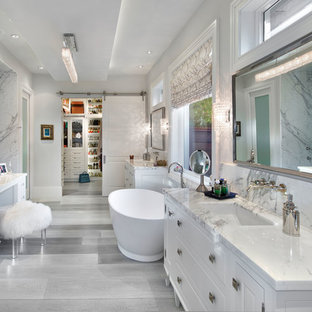 На фото: главная ванная комната в классическом стиле с врезной раковиной, белыми фасадами, отдельно стоящей ванной, белыми стенами и фасадами с выступающей филенкой с