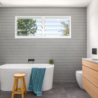 Design ideas for a contemporary kids bathroom in Sydney with furniture-like cabinets, light wood cabinets, a freestanding tub, blue tile, gray tile, matchstick tile, white walls, cement tiles, an undermount sink, engineered quartz benchtops, grey floor, grey benchtops and a one-piece toilet.