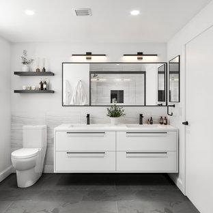 Foto de cuarto de baño minimalista con armarios con paneles lisos, puertas de armario blancas, paredes blancas, lavabo bajoencimera, suelo gris y encimeras blancas
