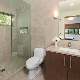На фото: ванная комната среднего размера в современном стиле с плоскими фасадами, темными деревянными фасадами, угловым душем, унитазом-моноблоком, бежевой плиткой, плиткой из известняка, бежевыми стенами, полом из известняка, душевой кабиной, врезной раковиной, столешницей из искусственного кварца, бежевым полом и душем с распашными дверями с