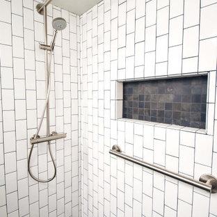 Idéer för att renovera ett litet funkis vit vitt badrum med dusch, med släta luckor, bruna skåp, en dusch i en alkov, en toalettstol med separat cisternkåpa, vit kakel, tunnelbanekakel, grå väggar, klinkergolv i keramik, ett integrerad handfat, svart golv och med dusch som är öppen