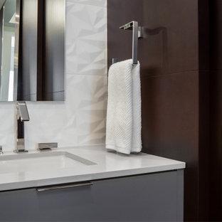 Inredning av ett modernt mellanstort vit vitt en-suite badrum, med släta luckor, grå skåp, en toalettstol med separat cisternkåpa, grå kakel, porslinskakel, vita väggar, klinkergolv i porslin, ett undermonterad handfat, bänkskiva i kvarts, grått golv och dusch med gångjärnsdörr