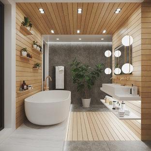 Inredning av ett modernt stort vit vitt badrum för barn, med ett fristående badkar, våtrum, en vägghängd toalettstol, grå kakel, skifferkakel, vita väggar, skiffergolv, ett avlångt handfat, bänkskiva i kvarts, grått golv och med dusch som är öppen