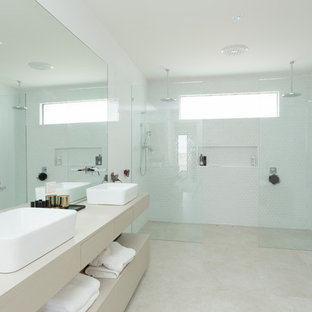 Modelo de cuarto de baño principal, actual, de tamaño medio, con armarios abiertos, puertas de armario de madera clara, ducha doble, baldosas y/o azulejos en mosaico, paredes blancas, suelo de travertino, lavabo sobreencimera, encimera de madera, suelo beige y ducha abierta