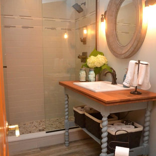 Inspiration for a small eclectic bathroom in Ottawa with open cabinets, turquoise cabinets, an alcove shower, a two-piece toilet, blue walls, porcelain floors, a drop-in sink, wood benchtops, grey floor and a hinged shower door.