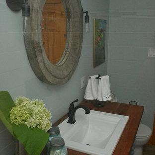 Imagen de cuarto de baño ecléctico, pequeño, con armarios abiertos, puertas de armario turquesas, ducha empotrada, sanitario de dos piezas, paredes azules, suelo de baldosas de porcelana, lavabo encastrado, encimera de madera, suelo gris y ducha con puerta con bisagras