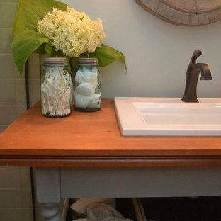 Modelo de cuarto de baño bohemio, pequeño, con armarios abiertos, puertas de armario turquesas, ducha empotrada, sanitario de dos piezas, paredes azules, suelo de baldosas de porcelana, lavabo encastrado, encimera de madera, suelo gris y ducha con puerta con bisagras
