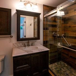Стильный дизайн: ванная комната среднего размера в стиле кантри с коричневыми фасадами, коричневой плиткой, плиткой под дерево, белыми стенами, темным паркетным полом, душевой кабиной, мраморной столешницей, коричневым полом, душем с раздвижными дверями, белой столешницей, тумбой под одну раковину и встроенной тумбой - последний тренд