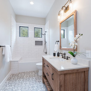 На фото: ванная комната среднего размера в стиле кантри с фасадами островного типа, коричневыми фасадами, ванной в нише, душем над ванной, унитазом-моноблоком, серой плиткой, керамической плиткой, серыми стенами, полом из керамической плитки, душевой кабиной, врезной раковиной, столешницей из кварцита, серым полом, шторкой для душа и белой столешницей с