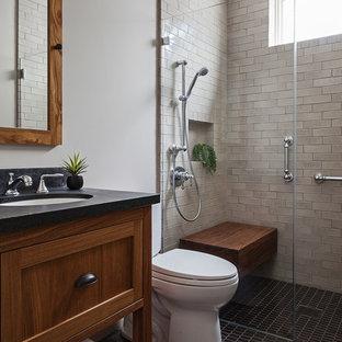 サンフランシスコの中くらいのおしゃれなバスルーム (浴槽なし) (落し込みパネル扉のキャビネット、濃色木目調キャビネット、バリアフリー、分離型トイレ、ベージュのタイル、サブウェイタイル、白い壁、セラミックタイルの床、アンダーカウンター洗面器、ソープストーンの洗面台、黒い床、オープンシャワー) の写真