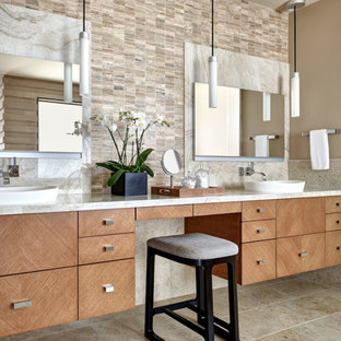 Southwest master beige tile and multicolored tile beige floor bathroom photo in Phoenix with flat-panel cabinets, light wood cabinets, beige walls, a vessel sink and beige countertops