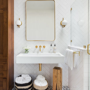 Photo of a transitional 3/4 bathroom in Albuquerque with white tile, a wall-mount sink, multi-coloured floor, medium wood cabinets, a corner shower, ceramic tile, white walls, terra-cotta floors and a hinged shower door.