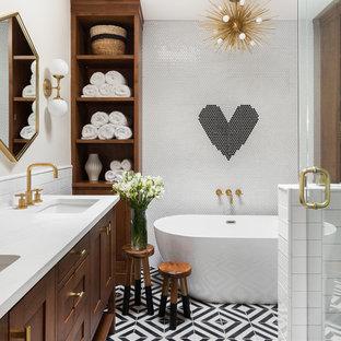 Cette photo montre une salle de bain principale chic avec une baignoire indépendante, un carrelage noir, un carrelage noir et blanc, un carrelage blanc, un lavabo encastré, un sol multicolore, un placard avec porte à panneau encastré, des portes de placard en bois brun, une douche d'angle, des carreaux de céramique, un mur blanc, un sol en carreaux de ciment, un plan de toilette en quartz, une cabine de douche à porte battante et un plan de toilette blanc.