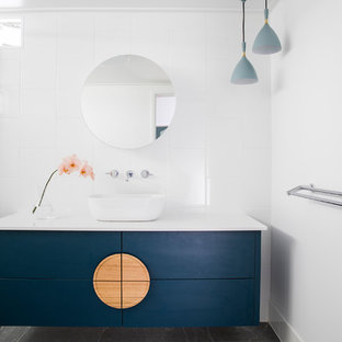 Inspiration for a mid-sized contemporary kids bathroom in Townsville with flat-panel cabinets, blue cabinets, white tile, ceramic tile, ceramic floors, grey floor, a hinged shower door, a vessel sink and white benchtops.