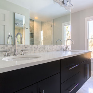 This is an example of a large contemporary master bathroom in Chicago with an undermount sink, flat-panel cabinets, multi-coloured tile, gray tile, white tile, mosaic tile, black cabinets, an alcove shower, grey walls, engineered quartz benchtops, a freestanding tub, a one-piece toilet, marble floors, white floor, a hinged shower door and yellow benchtops.