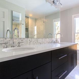 Bild på ett stort funkis gul gult en-suite badrum, med ett undermonterad handfat, släta luckor, flerfärgad kakel, grå kakel, vit kakel, mosaik, svarta skåp, en dusch i en alkov, grå väggar, bänkskiva i kvarts, ett fristående badkar, en toalettstol med hel cisternkåpa, marmorgolv, vitt golv och dusch med gångjärnsdörr