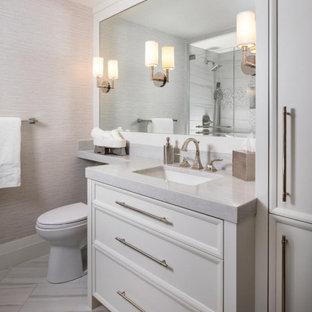 Foto på ett mellanstort maritimt grå badrum för barn, med luckor med infälld panel, vita skåp, en dusch i en alkov, en toalettstol med hel cisternkåpa, grå kakel, porslinskakel, grå väggar, klinkergolv i porslin, ett integrerad handfat, bänkskiva i kvarts, grått golv och dusch med gångjärnsdörr