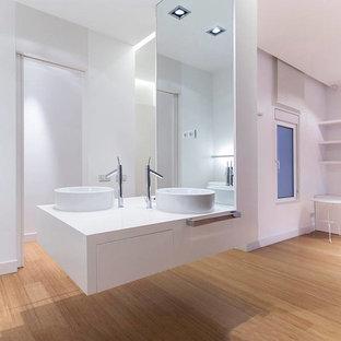Diseño de cuarto de baño principal, moderno, grande, con armarios con paneles lisos, puertas de armario blancas, paredes blancas, suelo de bambú, lavabo sobreencimera y encimera de cuarzo compacto