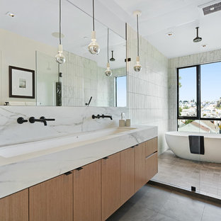 Large trendy master white tile ceramic floor bathroom photo in San Francisco with flat-panel cabinets, medium tone wood cabinets, white walls, a trough sink, marble countertops and white countertops