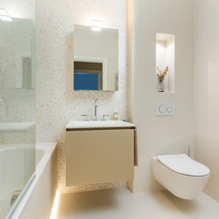 Design ideas for a small contemporary bathroom in London with glass-front cabinets, beige cabinets, a built-in bath, a shower/bath combination, a wall mounted toilet, beige tiles, mosaic tiles, beige walls, porcelain flooring, an integrated sink, glass worktops, beige floors, a hinged door, white worktops, a wall niche, a single sink, a floating vanity unit and a drop ceiling.