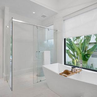 Пример оригинального дизайна: главная ванная комната среднего размера в современном стиле с плоскими фасадами, светлыми деревянными фасадами, отдельно стоящей ванной, открытым душем, унитазом-моноблоком, серой плиткой, керамогранитной плиткой, белыми стенами, полом из керамогранита, настольной раковиной, столешницей из искусственного кварца, белым полом, душем с раздвижными дверями, белой столешницей, унитазом, тумбой под две раковины, напольной тумбой и многоуровневым потолком