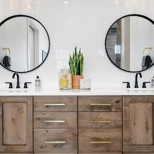 ボイシの大きいカントリー風おしゃれなマスターバスルーム (シェーカースタイル扉のキャビネット、中間色木目調キャビネット、置き型浴槽、アルコーブ型シャワー、磁器タイル、白い壁、大理石の床、アンダーカウンター洗面器、クオーツストーンの洗面台、白い床、オープンシャワー、白い洗面カウンター、白いタイル) の写真