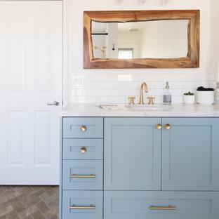 Foto på ett mellanstort lantligt vit badrum med dusch, med skåp i shakerstil, turkosa skåp, vit kakel, tunnelbanekakel, klinkergolv i småsten, ett undermonterad handfat, bänkskiva i kvarts, grått golv och dusch med skjutdörr