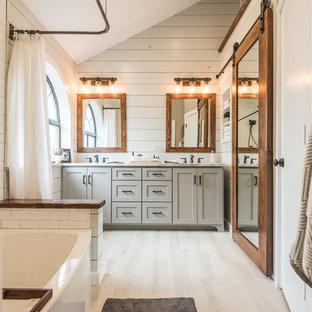 Modelo de cuarto de baño principal, campestre, de tamaño medio, con armarios estilo shaker, puertas de armario grises, bañera empotrada, combinación de ducha y bañera, sanitario de una pieza, baldosas y/o azulejos grises, baldosas y/o azulejos blancos, paredes grises, suelo de baldosas de porcelana, lavabo bajoencimera, encimera de granito, baldosas y/o azulejos de cemento y ducha con cortina
