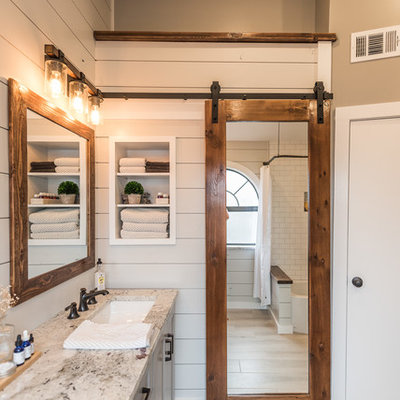 Bathroom - mid-sized cottage master gray tile and porcelain tile porcelain tile bathroom idea in Dallas with shaker cabinets, gray cabinets, a one-piece toilet, gray walls, an undermount sink and granite countertops