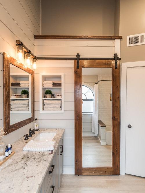 Salle de bain avec un plan de toilette en granite et un combiné ...