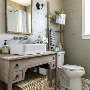 Ejemplo de cuarto de baño principal, de estilo de casa de campo, pequeño, con armarios tipo mueble, puertas de armario de madera clara, bañera con patas, lavabo sobreencimera, sanitario de dos piezas, paredes grises, suelo de azulejos de cemento, suelo negro y encimeras marrones