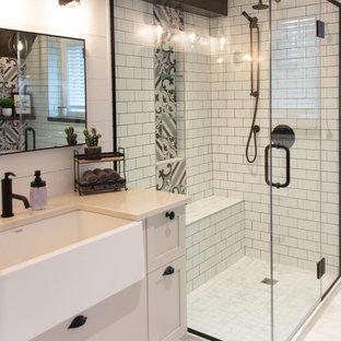 オタワの大きいカントリー風おしゃれなバスルーム (浴槽なし) (シェーカースタイル扉のキャビネット、ベージュのキャビネット、コーナー設置型シャワー、一体型トイレ、白いタイル、サブウェイタイル、白い壁、セラミックタイルの床、オーバーカウンターシンク、珪岩の洗面台、白い床、開き戸のシャワー、ベージュのカウンター) の写真