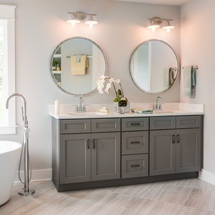 This is an example of a country 3/4 bathroom in Philadelphia with shaker cabinets, grey cabinets, a freestanding tub, grey walls, an undermount sink and grey floor.