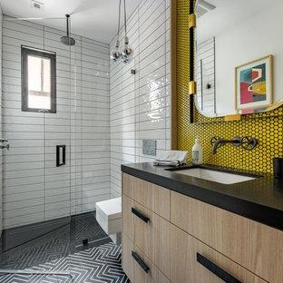 Réalisation d'une douche en alcôve design avec un placard à porte plane, des portes de placard en bois clair, un carrelage jaune, carrelage en mosaïque, un lavabo encastré, un sol noir et un plan de toilette noir.