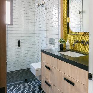 Ejemplo de cuarto de baño con ducha, actual, con armarios con paneles lisos, puertas de armario de madera clara, ducha a ras de suelo, sanitario de pared, baldosas y/o azulejos blancos, baldosas y/o azulejos amarillos, baldosas y/o azulejos en mosaico, lavabo bajoencimera, suelo negro, ducha con puerta con bisagras y encimeras negras