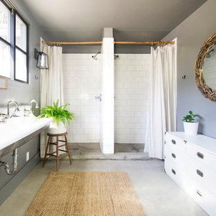 Imagen de cuarto de baño con ducha, de estilo de casa de campo, con armarios tipo mueble, puertas de armario blancas, ducha doble, baldosas y/o azulejos blancos, baldosas y/o azulejos de cemento, paredes grises, suelo de cemento, lavabo suspendido, suelo gris y ducha con cortina